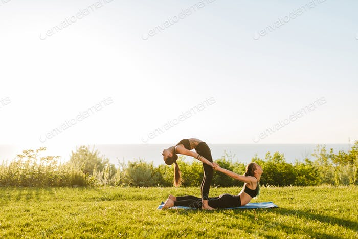 Photo of two young ladies in black sporty tops and leggings training yoga poses together on grass