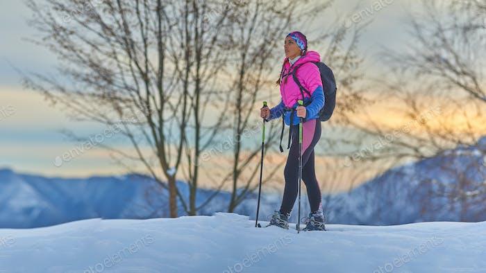 Woman rests during a snowshoe trek