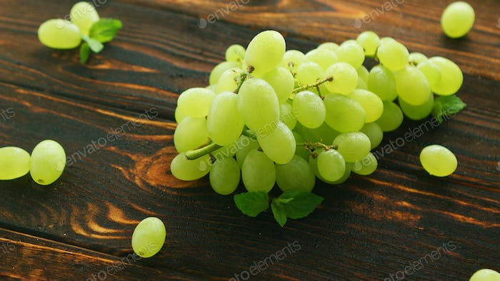 Grapes on branch on dark table
