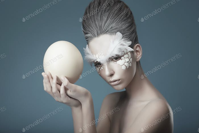 Fashion model holding ostrich's egg