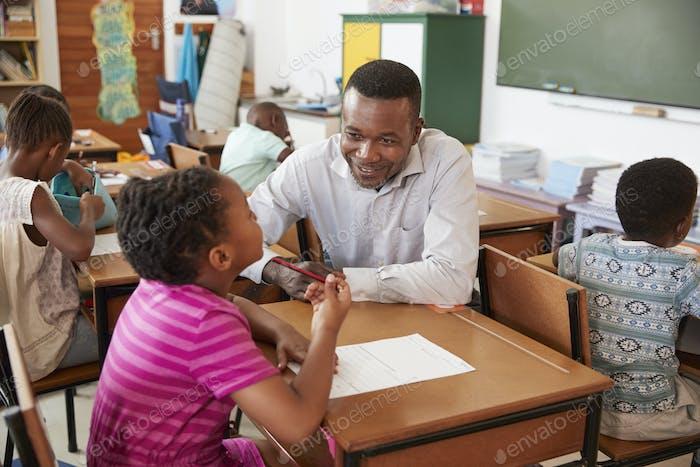 Black male teacher helping elementary school girl in class