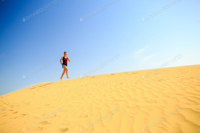 Young woman running on sand desert dunes