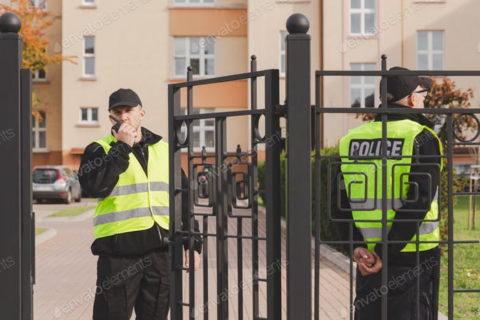 Two policemen stand in front of the entrance gate to the house