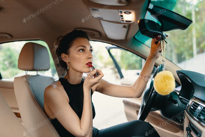 Young elegant woman looking in the car view mirror while applying makeup, lipstick on the lips