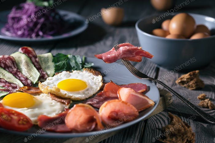 Fried eggs with bacon and vegetables on a blue plate