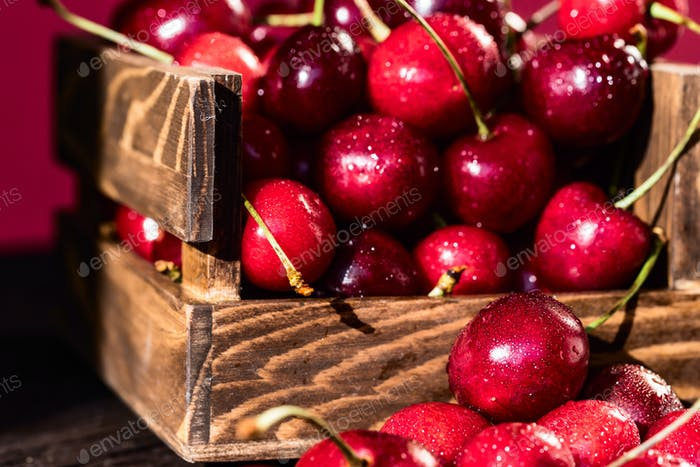 Fresh sweet cherries in a wooden box close
