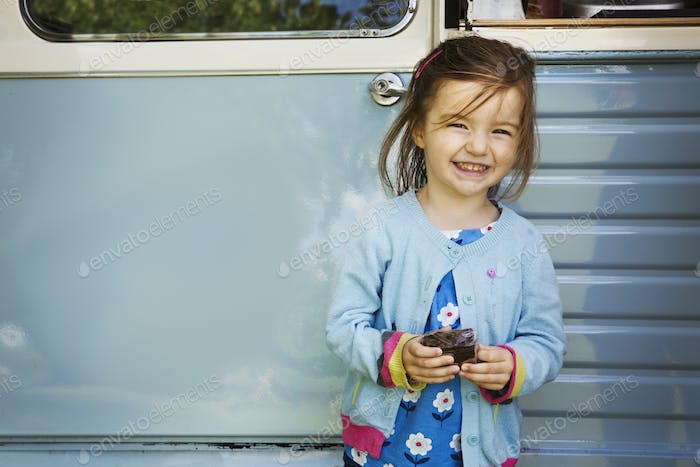 Smiling girl standing in front of blue mobile coffee shop, holding chocolate brownie.