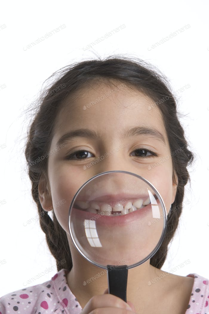 Little Girl Shows Her Teeth Through A Magnifying Glass