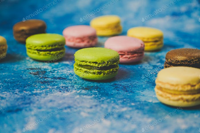 Variety of colorful macarons over a blue background