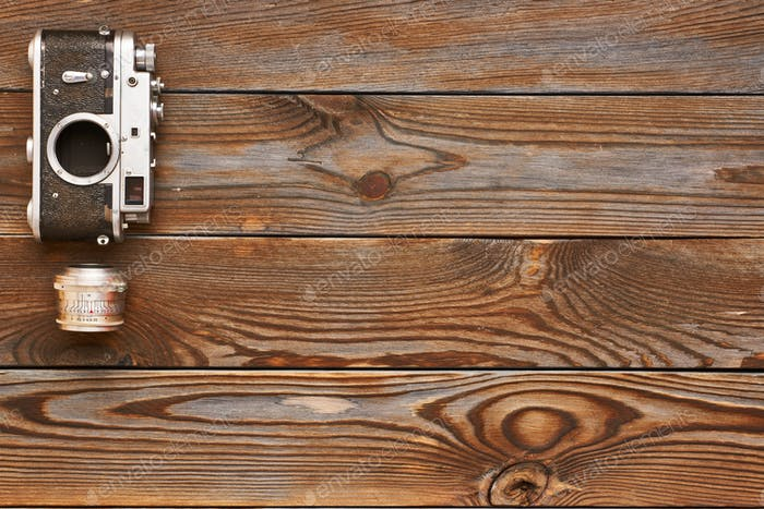Vintage old camera and lens on wooden background