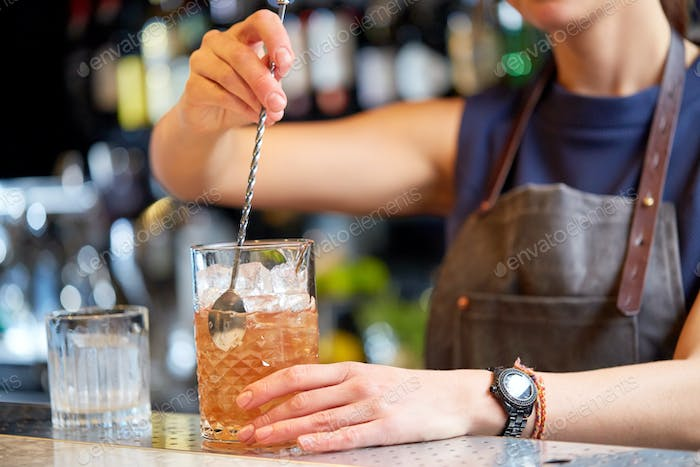 bartender with cocktail stirrer and glass at bar
