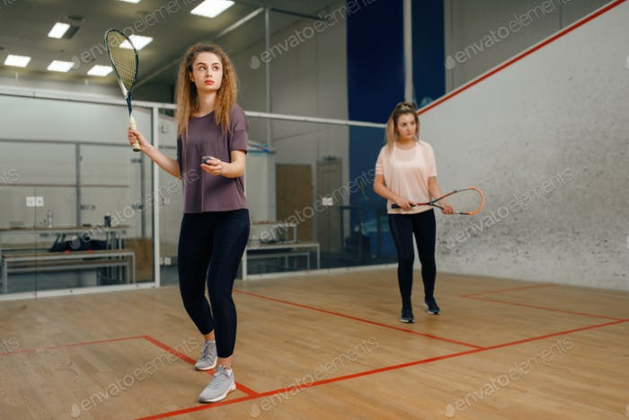 Two players with squash racket playing on court