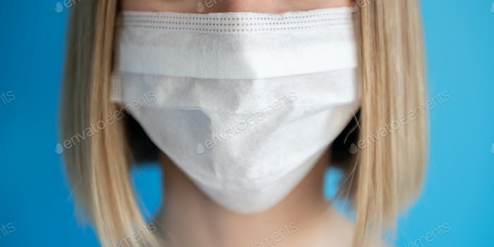 Nurse or doctor with face mask. Close up portrait of young caucasian woman model on blue background