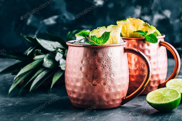 Iced Cold Moscow Mule cocktail with lime and pineapple on dark background