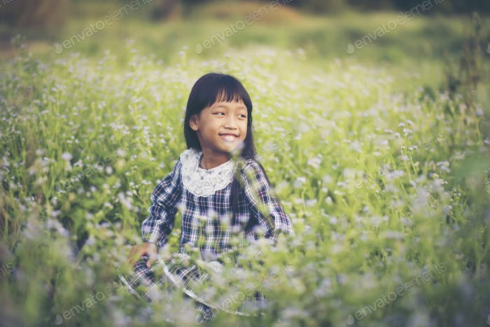 Happy girl sitting on the meadow
