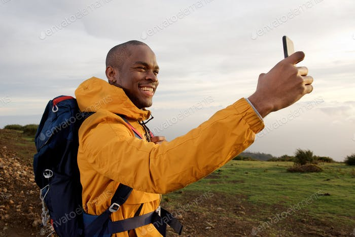 smiling young african american male hiker taking selfie outdoors