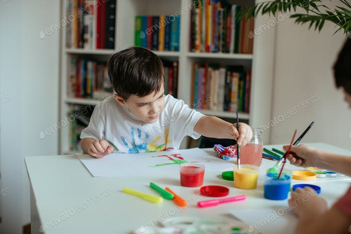 Left handed little boy reaching for paint with paintbrush in his hand.