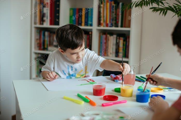 Linkshänder kleiner Junge greift nach Farbe mit Pinsel in der Hand.