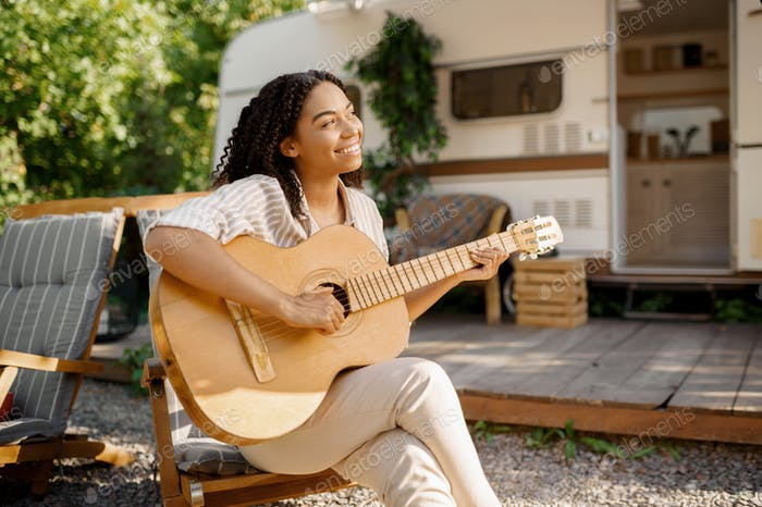 Woman with guitar near the rv, camping in trailer