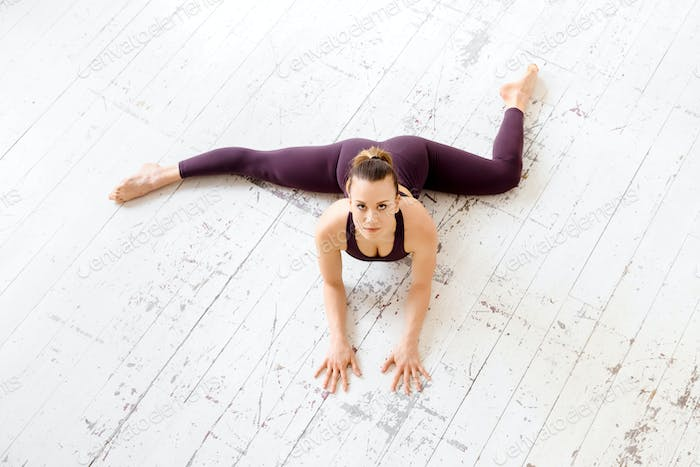 High angle of a woman doing a half frontal split