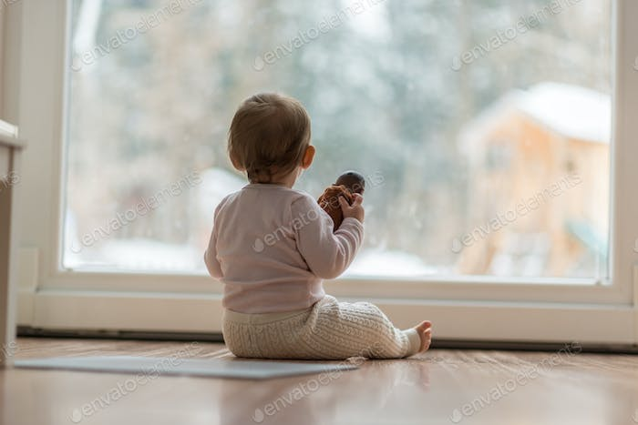 Little baby girl watching the snow outdoors