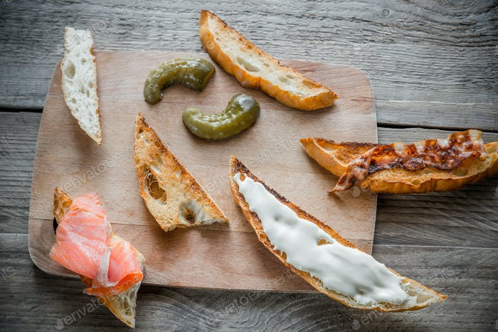 Toasts with different toppings on the wooden board
