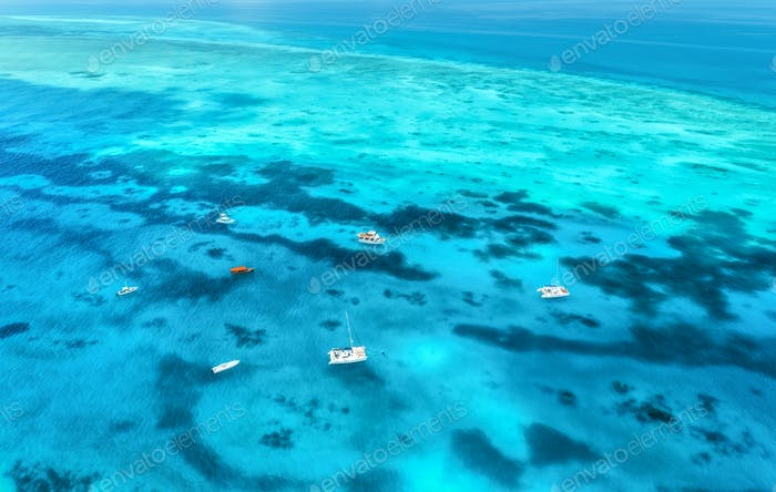 Aerial view of luxury yachts and fishing boats in clear blue sea