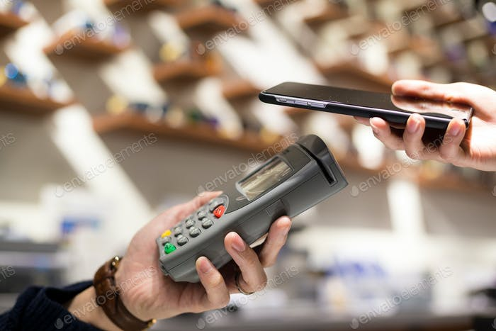 Woman checkout by mobile phone by NFC