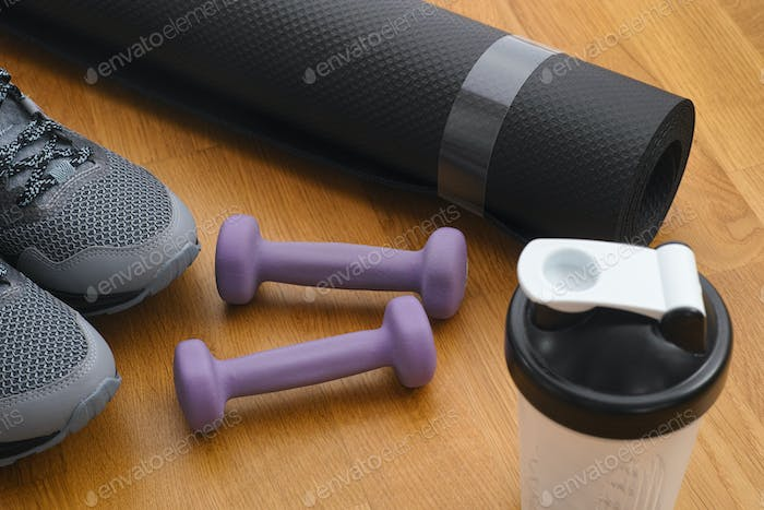 Protein shaker, dumbbells, sport shoes and exercise mat on the floor