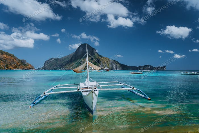 Cadlao panorama with Traditional filippino banca boat in front. Exotic tropical El Nido bay, Palawan