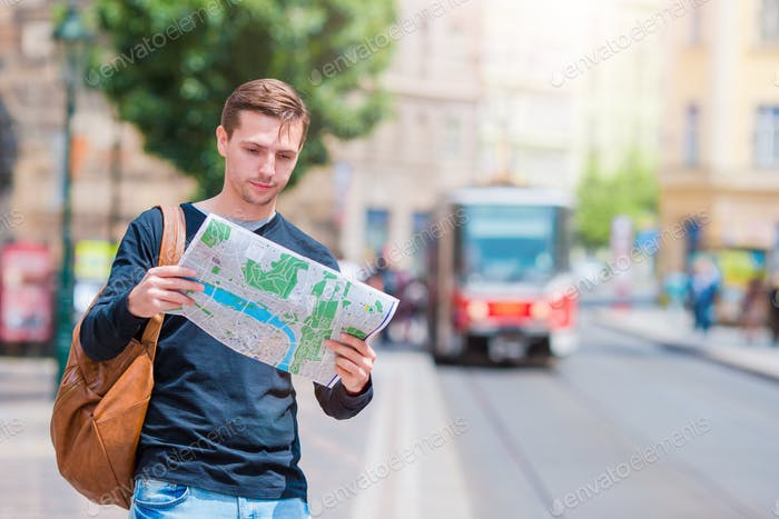 Young man in sunglasses with a city map and backpack in Europe. Caucasian tourist looking at the map
