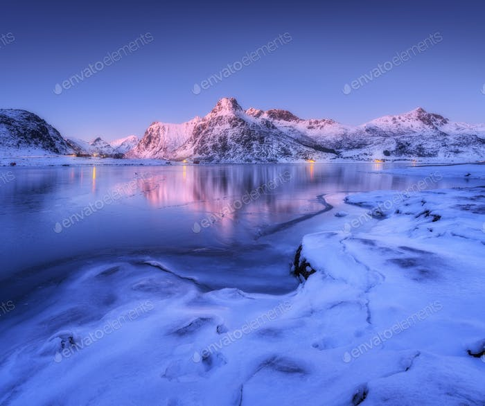 Frozen sea coast and beautiful snow covered mountains at dusk