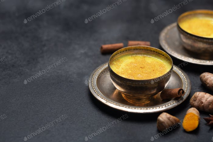 Golden Turmeric Milk On The Black Background With Ingredients