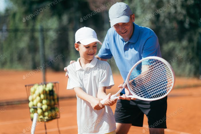 Tennis Lesson. Smiling Coach Explaining Tennis Technique to a Boy