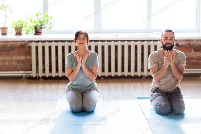 man and woman meditating at yoga studio