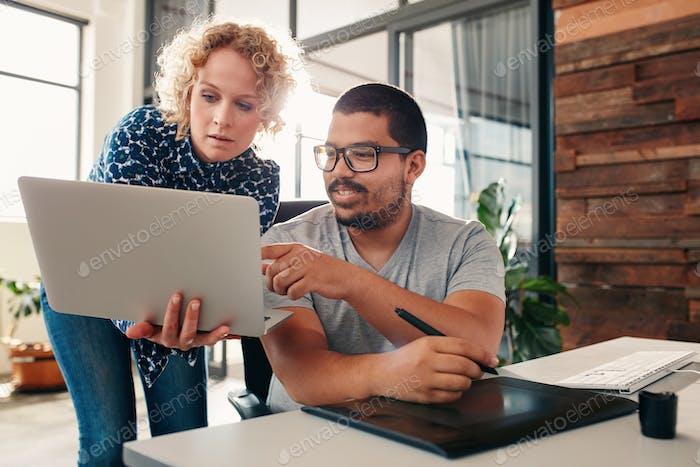 Graphic designers cooperating in design studio