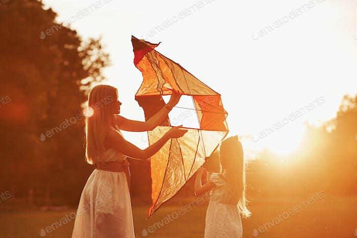 Machen Sie sich bereit. Mutter und Tochter haben Spaß mit Drachen auf dem Feld. Schöne Natur