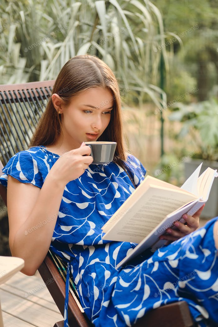 Young attractive brown haired woman in dress drinking coffee and thoughtfully reading book in park
