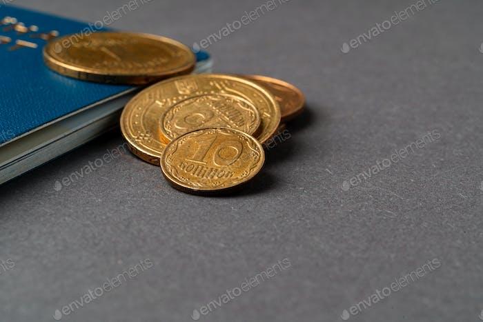 Pasaporte ucraniano con monedas hryvnia ucranianas. Concepto de pobreza e inmigración