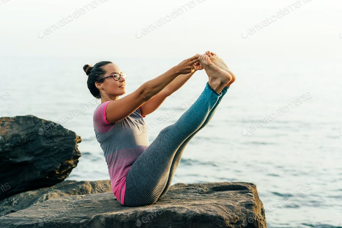 Young sporty woman stretching and balancing in yoga position by the sea.