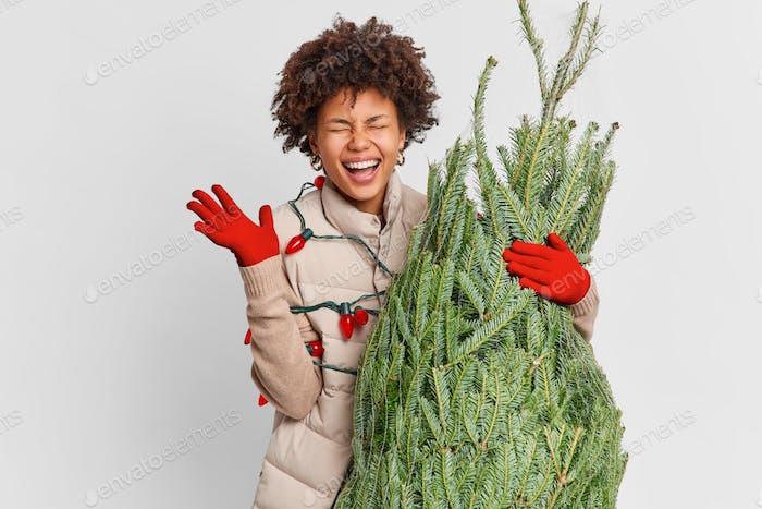Overjoyed dark skinned woman raises hand ans laughs hapily returns home from Christmas fair carries