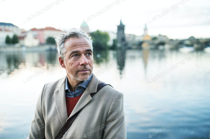 Mature businessman standing by river Vltava in Prague city. Copy space.