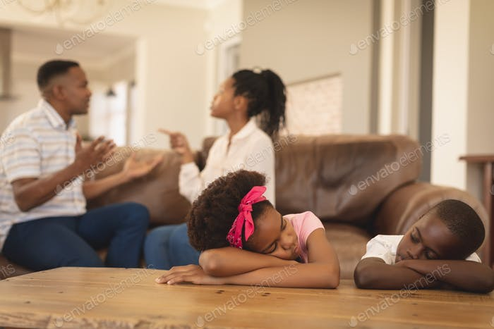 Front view of African American children leaning on table while parents arguing on the sofa at home