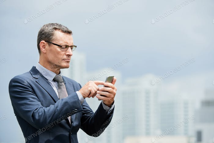 Mature entrepreneur with smartphone