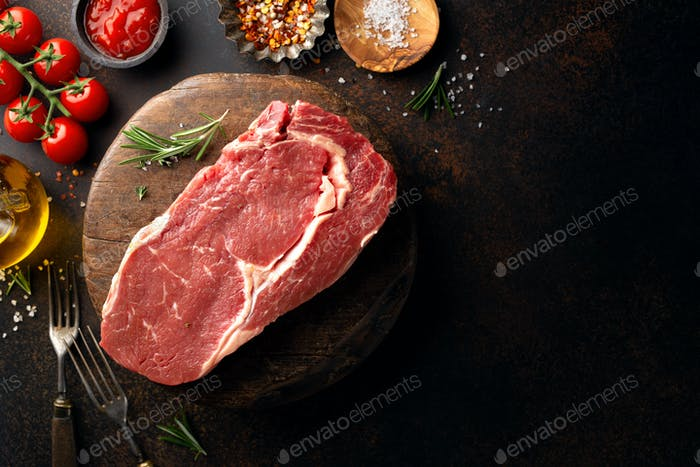 Raw beef steak with ingredients on table