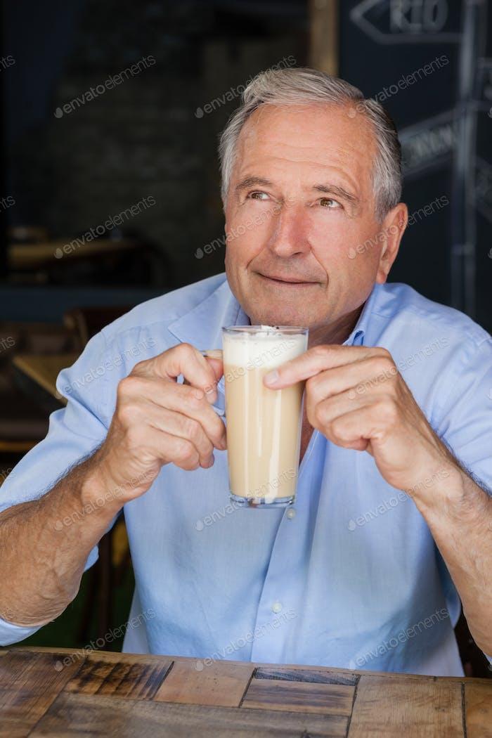 Senior Mann hält kalten Kaffee beim Sitzen am Tisch