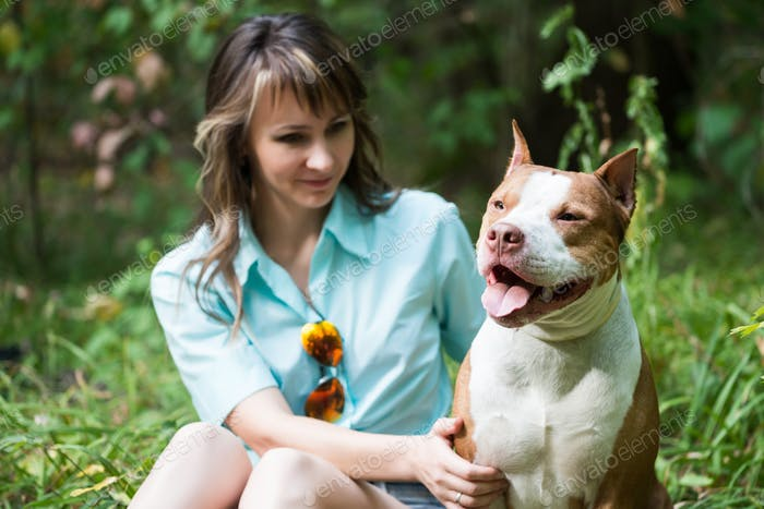 Beautiful woman sitting on grass with dog Pit bull