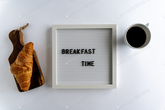 Letterboard With Words That Spell Breakfast Time, with a croissant and a cup of coffee , on white