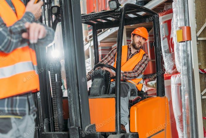 worker in safety vest and helmet sitting in forklift machine in storage