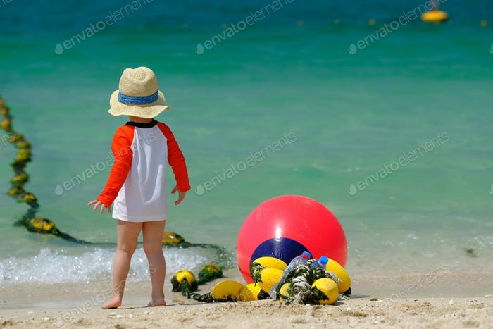 Two year old toddler boy walking on beach